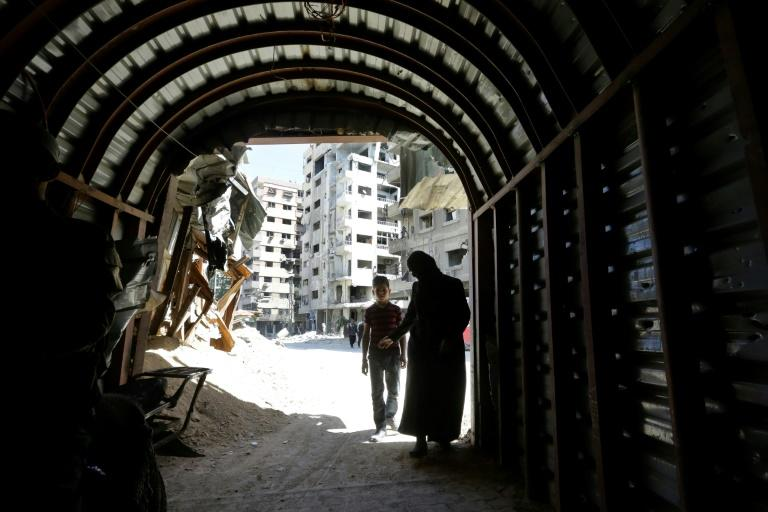Syrians enter a tunnel leading to an underground hospital in Douma, in eartern Ghouta, a subterranean network of tunnels and makeshift wards and operating rooms beneath the former rebel enclave (AFP Photo/LOUAI BESHARA)