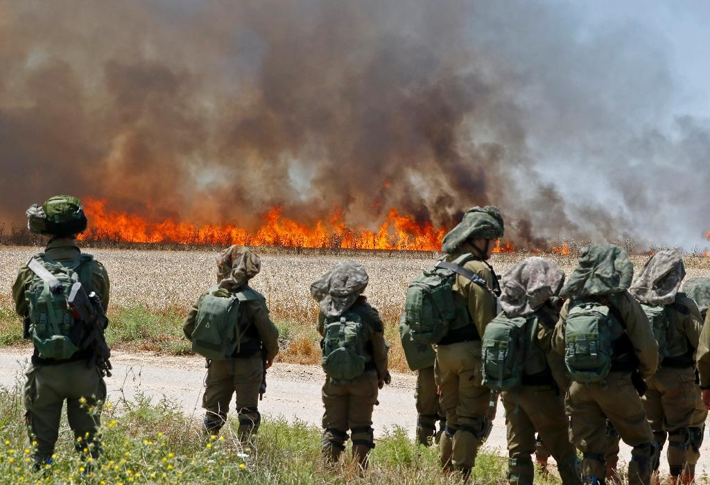 Israeli soldiers walk amidst smoke from a fire in a wheat field near the Kibbutz of Nahal Oz, along the border with the Gaza Strip (AFP Photo/JACK GUEZ)