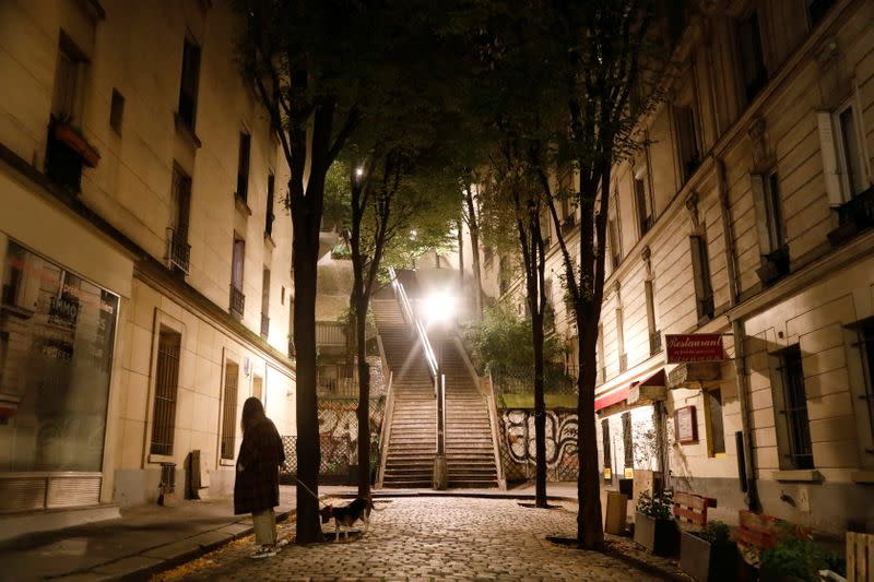 A woman walks her dog in Montmartre during the late-night curfew due to restrictions against the spread of the coronavirus disease (COVID-19) in Paris