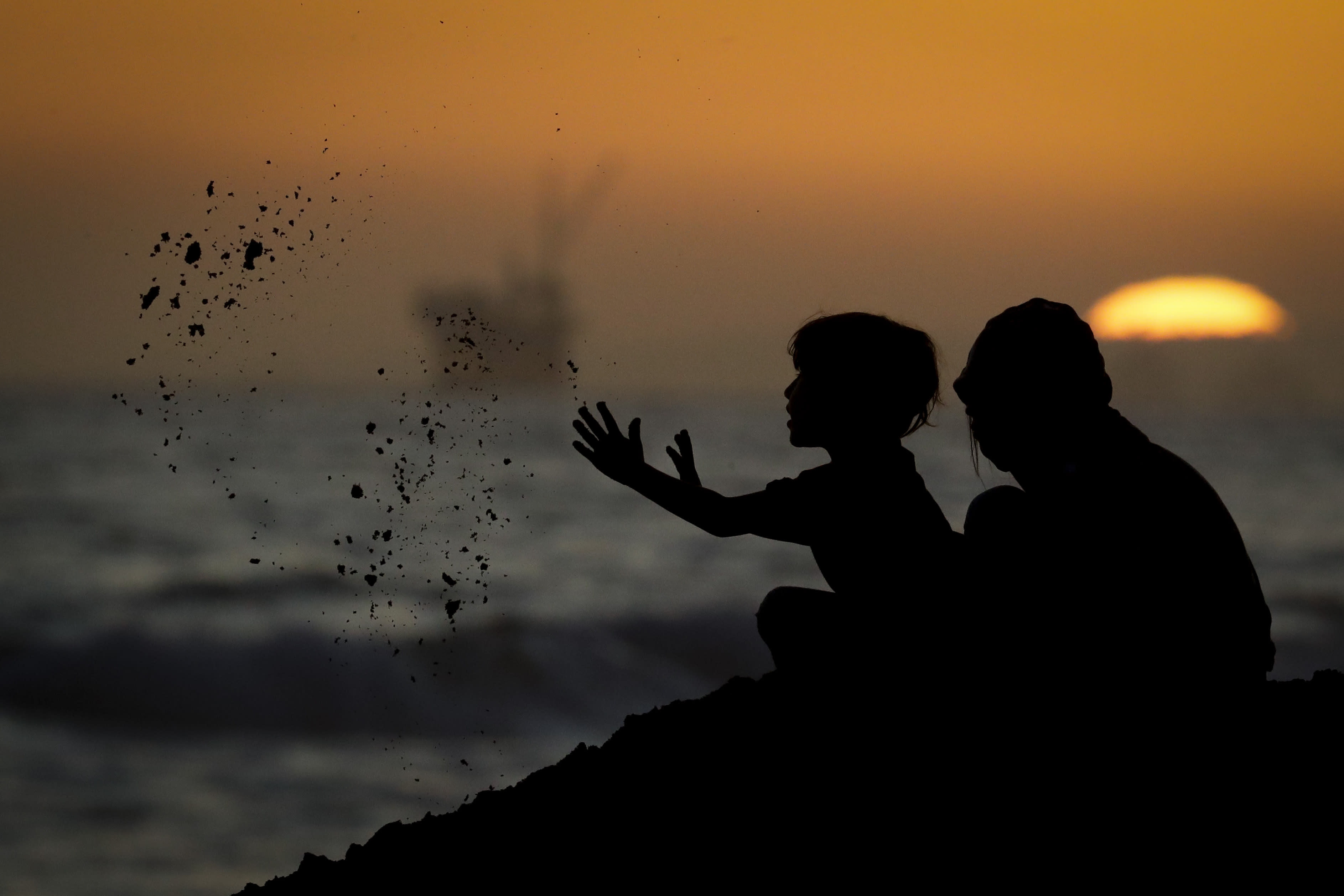 Youngsters play in the sand Tuesday, April 21, 2020, in Huntington Beach, Calif. Warm temperatures are predicted for Southern California by the end of the week. (AP Photo/Chris Carlson)