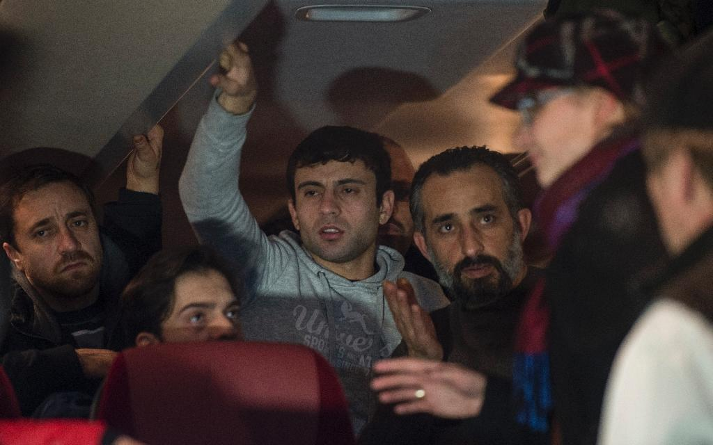 Refugees who have been granted asylum status in Germany speak to officials on a bus in front of the Chancellery in Berlin on January 14, 2016 (AFP Photo/John MacDougall)