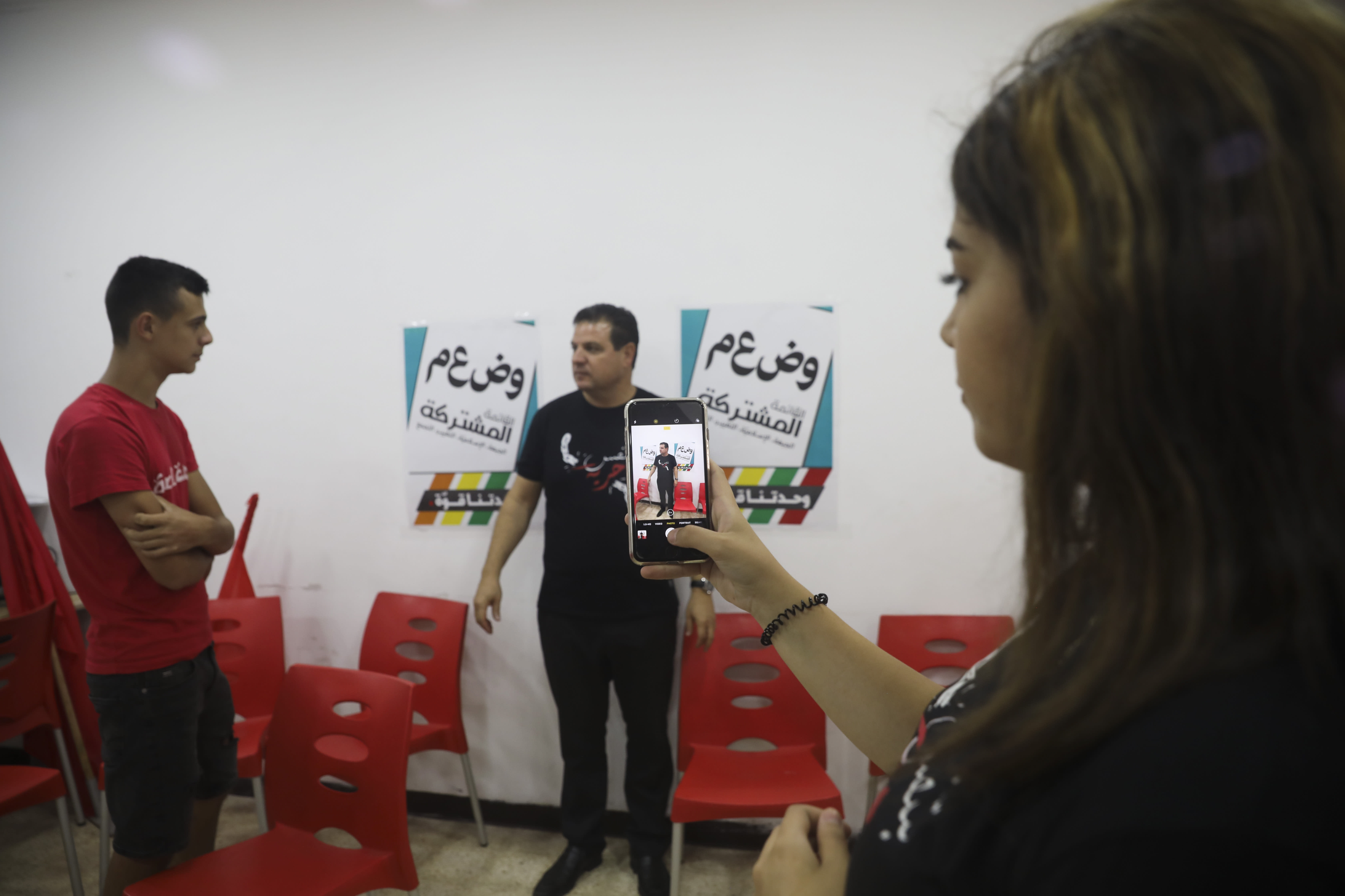 In this Thursday, Aug. 29, 2019 photo, an activist takes a photo of Ayman Odeh, the leader of the Arab Joint List parties, during a campaign meeting in Nazareth, Israel. Odeh has shaken up Israel's election campaign by offering to sit in a moderate coalition government _ a development that would upend decades of convention that has relegated Arab parties to the sidelines and could bring down Prime Minister Benjamin Netanyahu. (AP Photo/Mahmoud Illean)