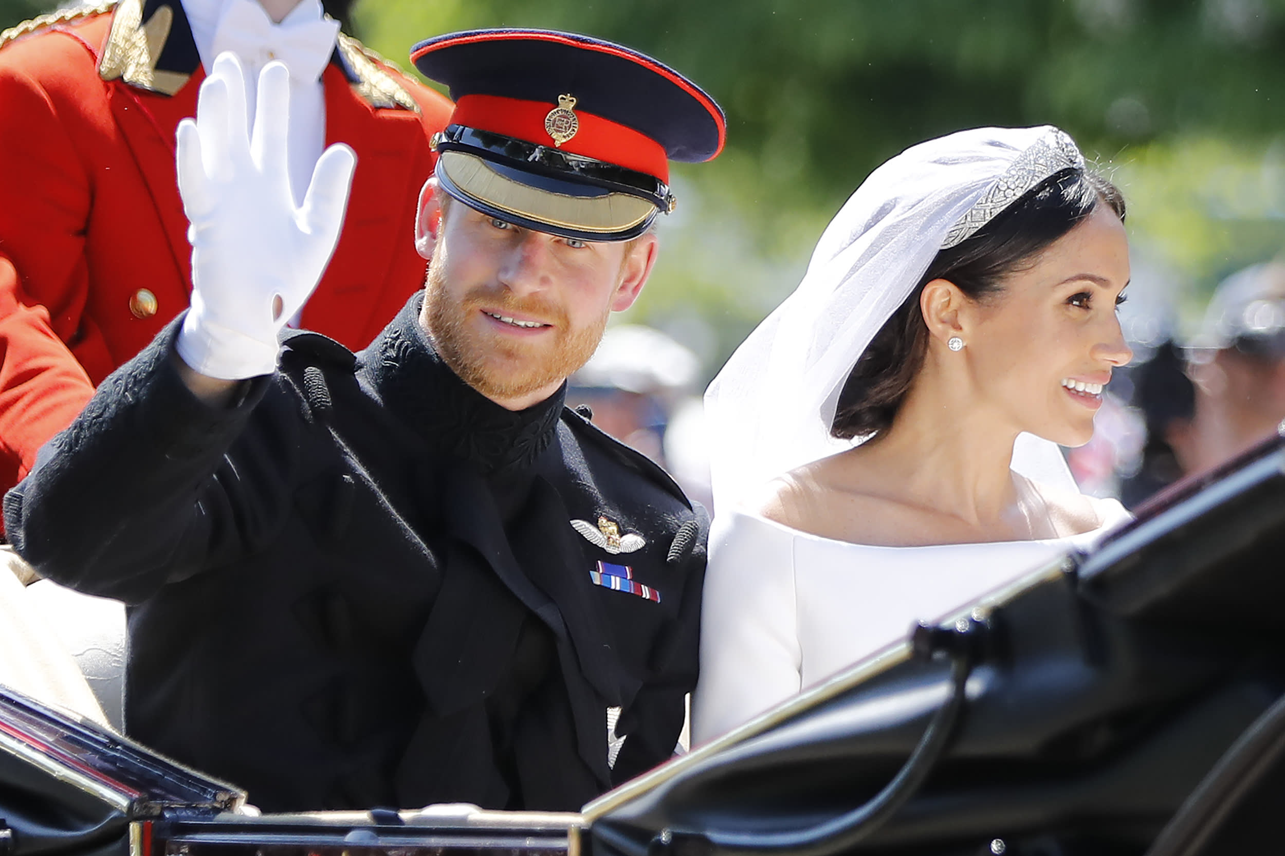 TOPSHOT - Britain's Prince Harry, Duke of Sussex and his wife Meghan, Duchess of Sussex wave from the Ascot Landau Carriage during their carriage procession on the Long Walk as they head back towards Windsor Castle in Windsor, on May 19, 2018 after their wedding ceremony. (Photo by Tolga AKMEN / AFP)        (Photo credit should read TOLGA AKMEN/AFP/Getty Images)
