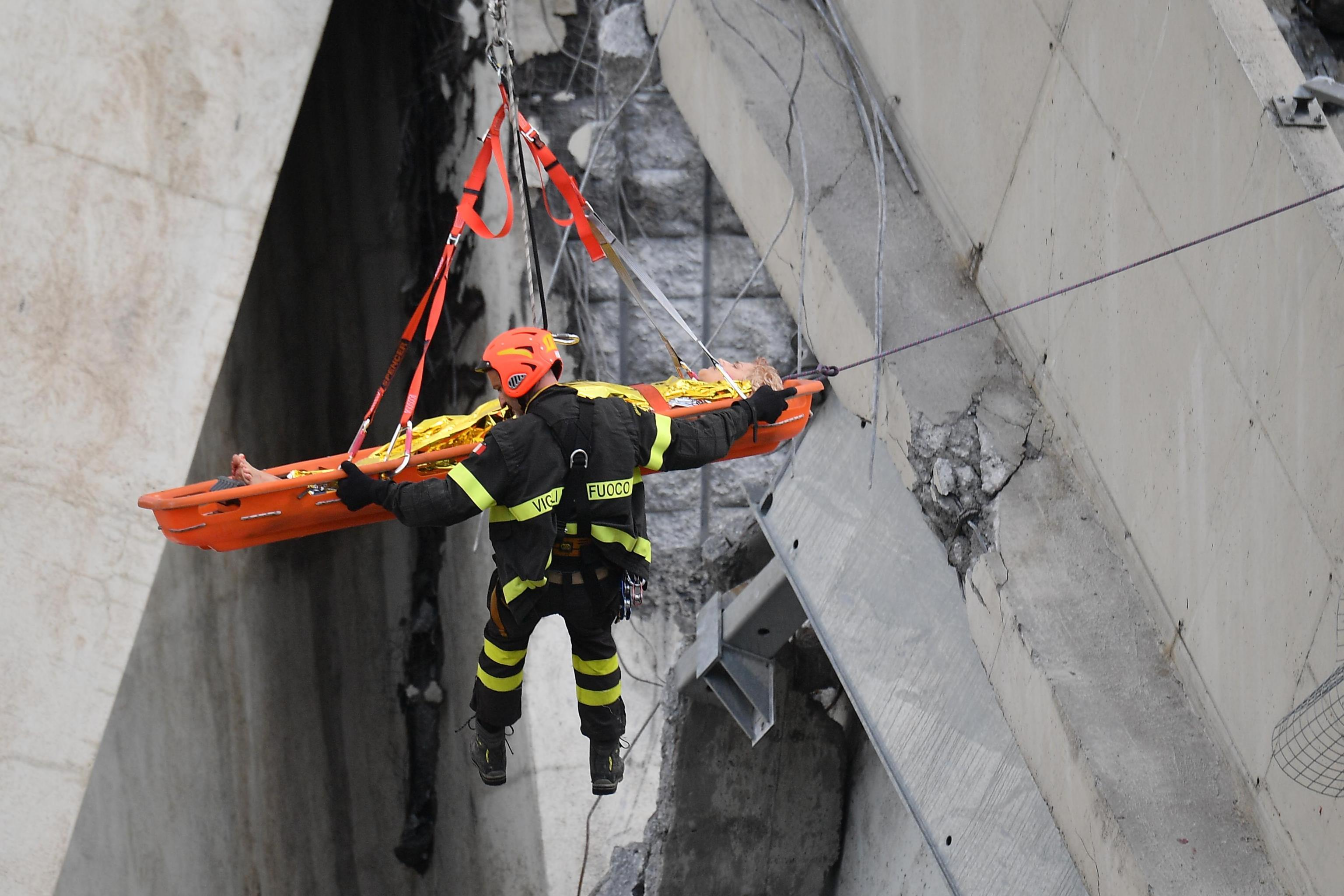 <p>Rescuers recover an injured person after a highway bridge collapsed in Genoa, Italy, Aug. 14,2018. (Photo: Luca Zennaro/EPA-EFE/REX/Shutterstock) </p>