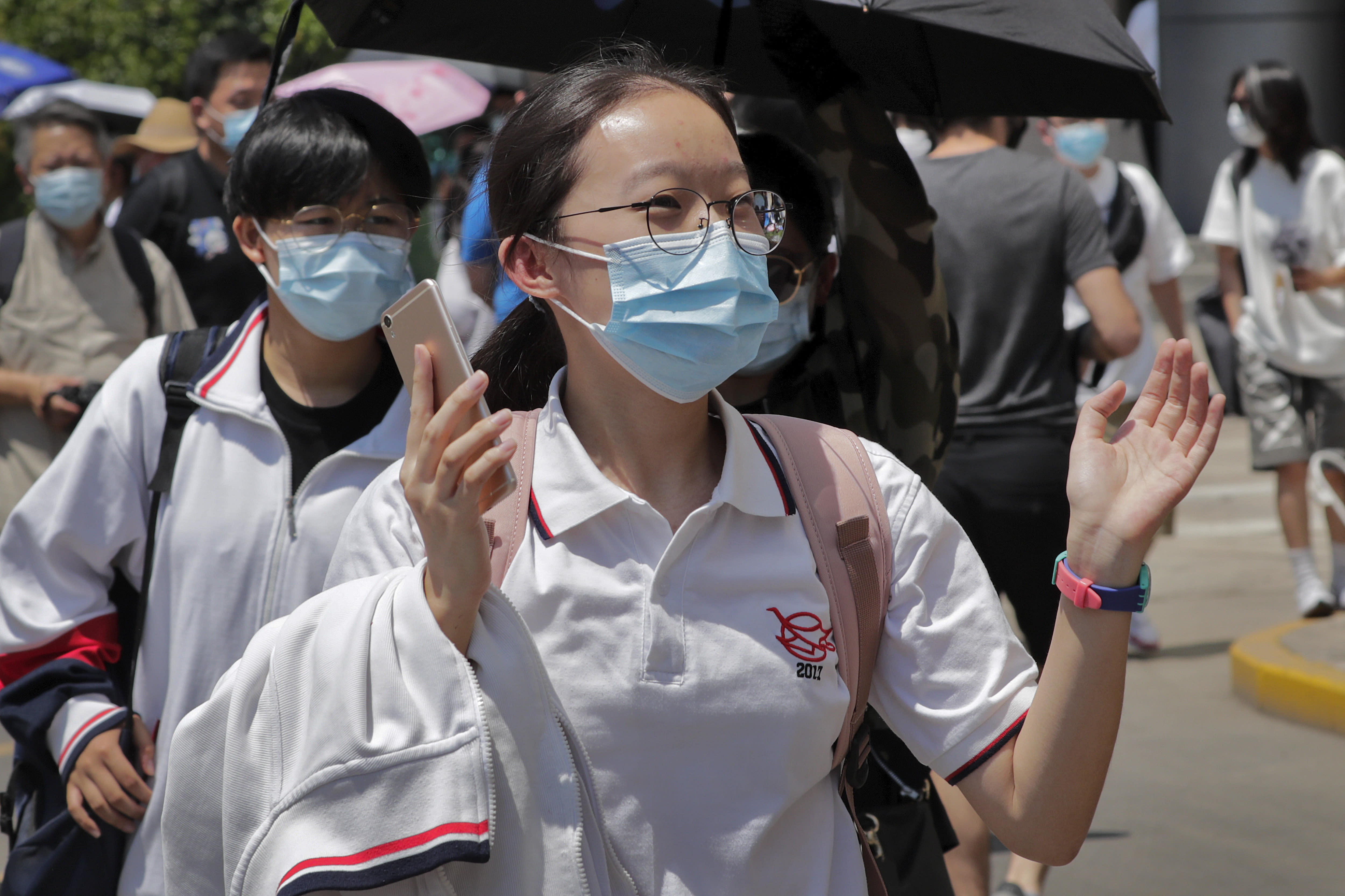 A student wearing a face mask to protect against the new coronavirus reacts as she leaves school after finishing the first day of China's national college entrance examinations, known as the gaokao, in Beijing, Tuesday, July 7, 2020. China's college entrance exams began in Beijing on Tuesday after being delayed by a month due to the coronavirus outbreak. (AP Photo/Andy Wong)