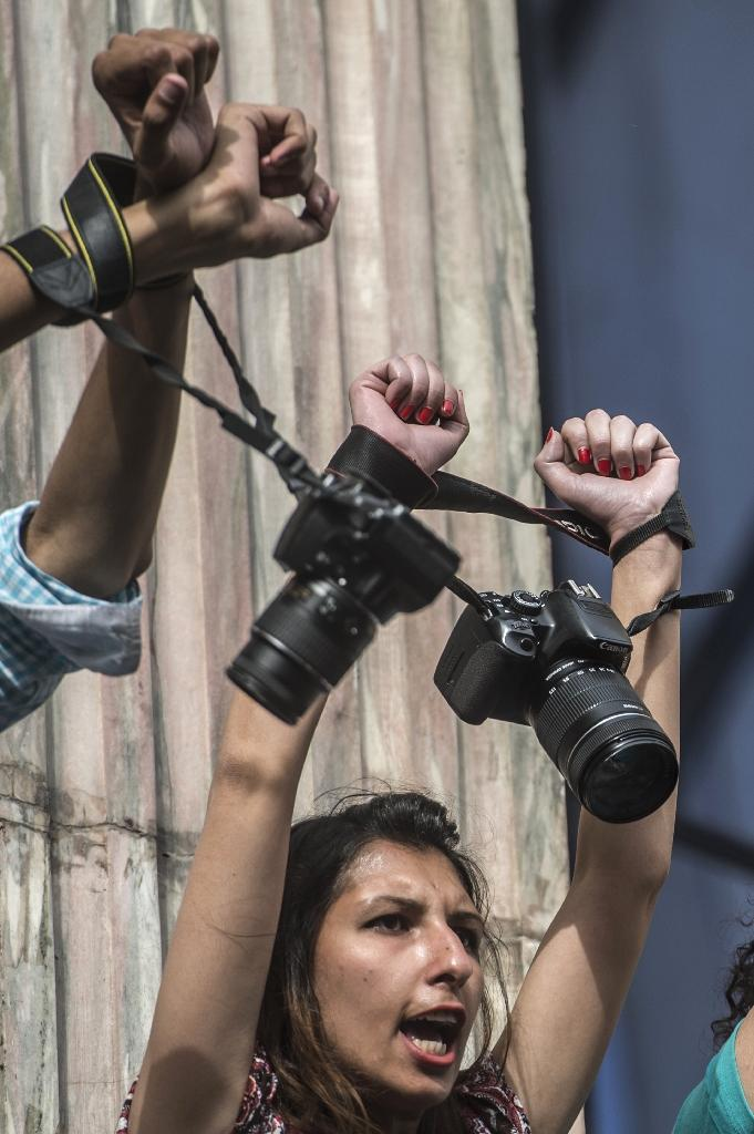 Egyptian photojournalists raise their cameras during a demonstration outside the Syndicate headquarters in Cairo on May 3, 2016 on the occasion of World Press Freedom day (AFP Photo/Khaled Desouki)