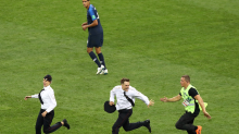 Fans rush the field during one of the most thrilling segments of the World Cup Final and stop play
