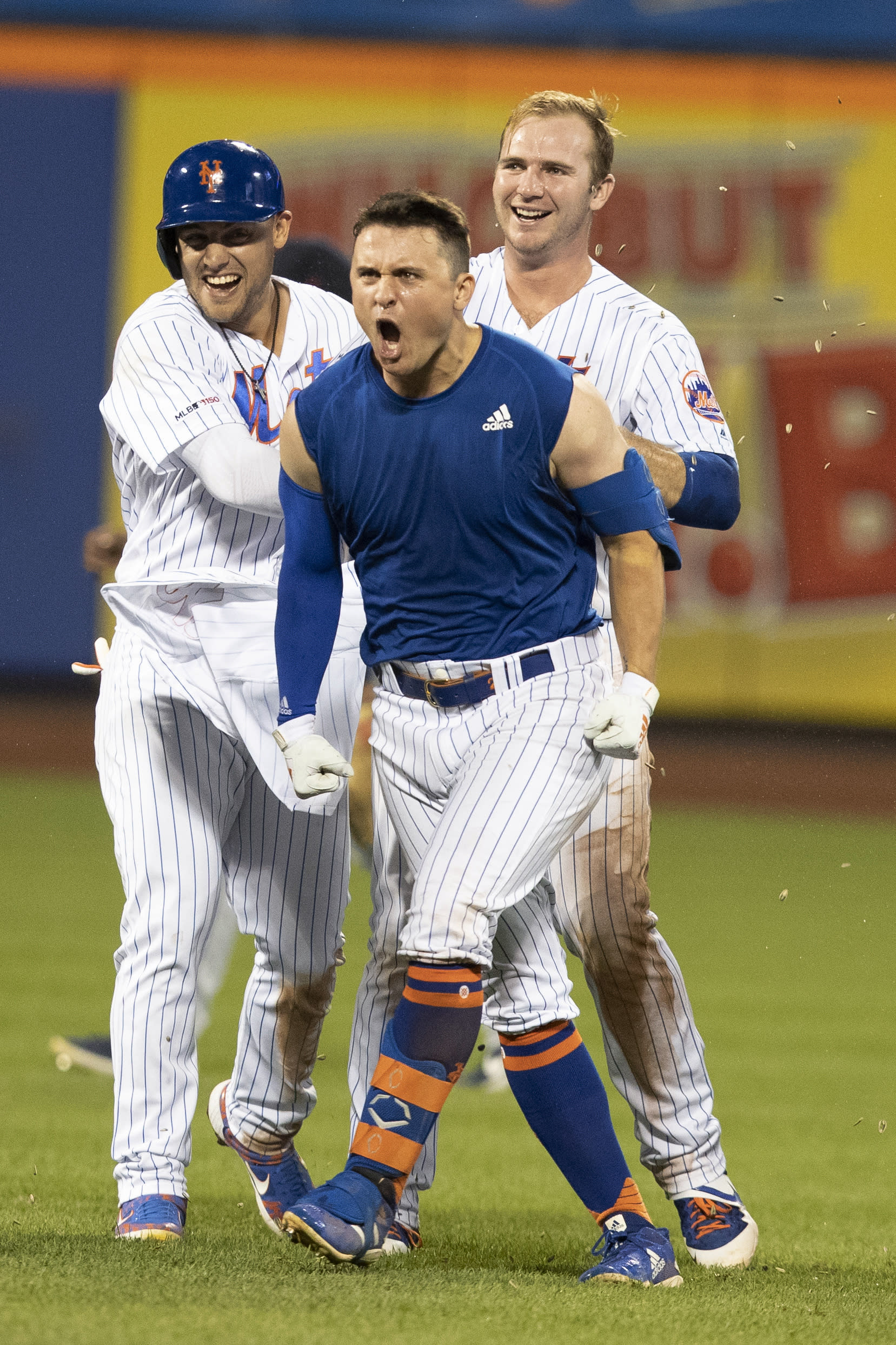 New York Mets' J.D. Davis reacts, center, is congratulated by teammates after he drove in the winning run in the 10th inning of the team's baseball game against the Cleveland Indians, Wednesday, Aug. 21, 2019, in New York. (AP Photo/Mary Altaffer)