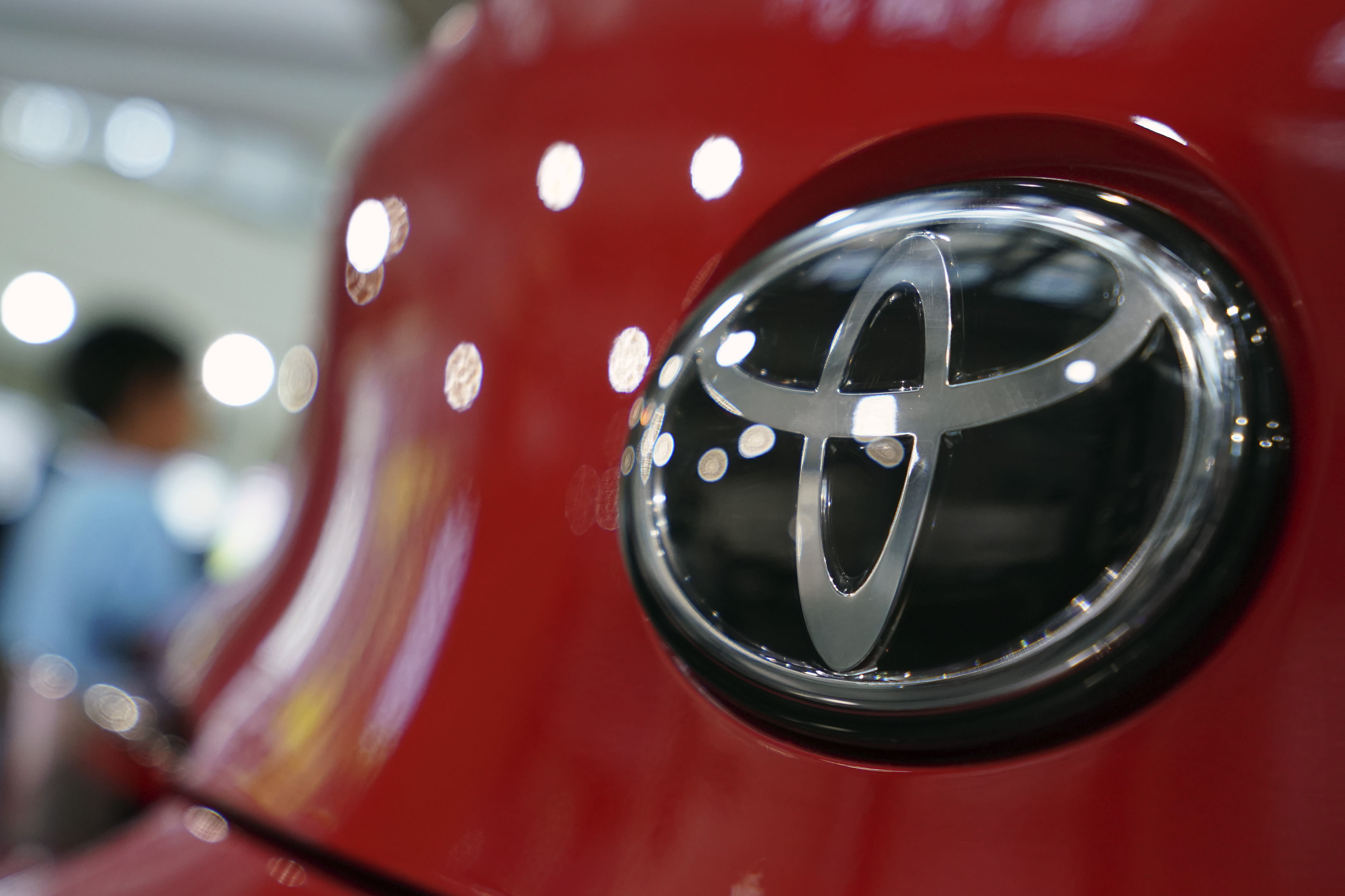 FILE - In this Aug. 2, 2019, file, photo, people walk by the logo of Toyota at a show room in Tokyo. Japan's top automaker Toyota has seen a 1% rise in July-September profit as vehicle sales grew around the world, according to Toyota's report on Thursday, Nov. 7, 2019. (AP Photo/Eugene Hoshiko, File)