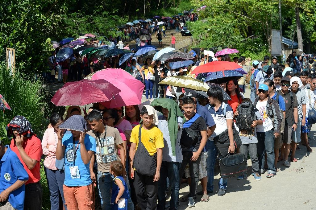 Residents and commuters queue up at a police checkpoint at the entrance to Iligan City on the southern island of of Mindanao on May 29, 2017, after local authorities locked down the city due to a terror threat (AFP Photo/Ted ALJIBE)