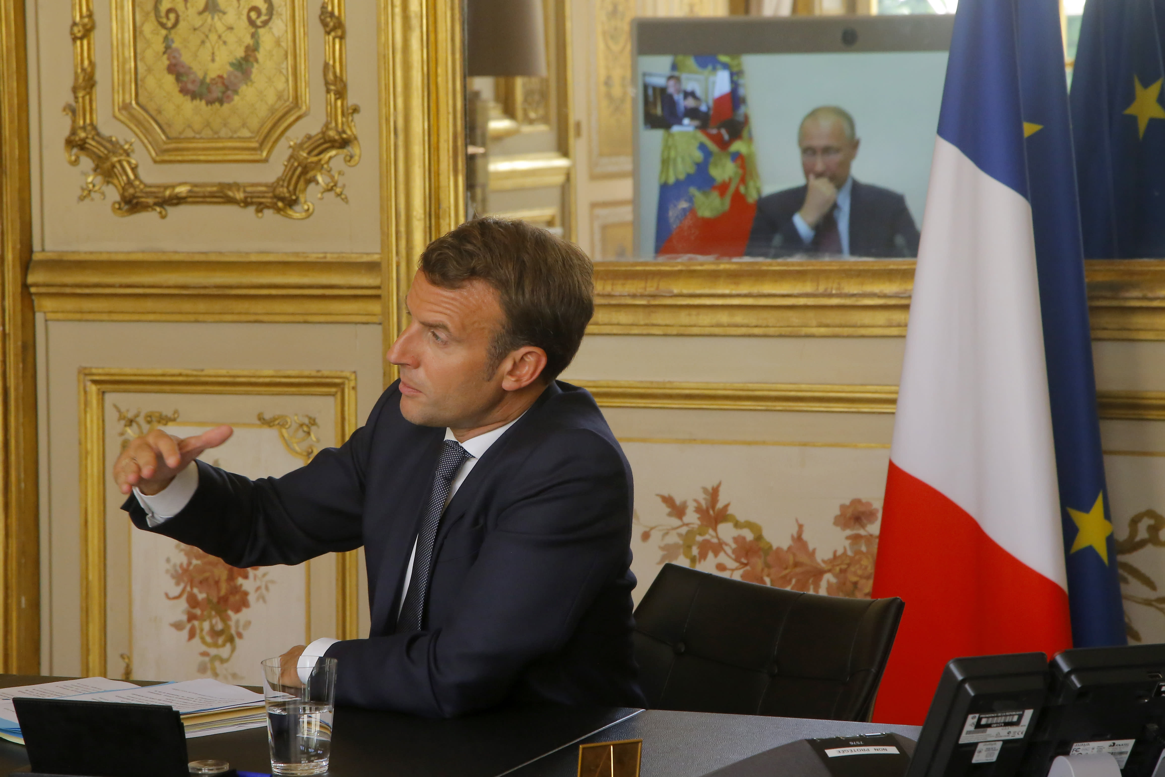 French President Emmanuel Macron talks to Russian President Vladimir Putin during a video conference Friday, June 26, 2020 at the Elysee Palace in Paris. Russian President Vladimir Putin holds video talks with French President Emmanuel Macron about the virus, Libya, Syria and relations with the U.S. under Donald Trump. (AP Photo/Michel Euler, Pool)