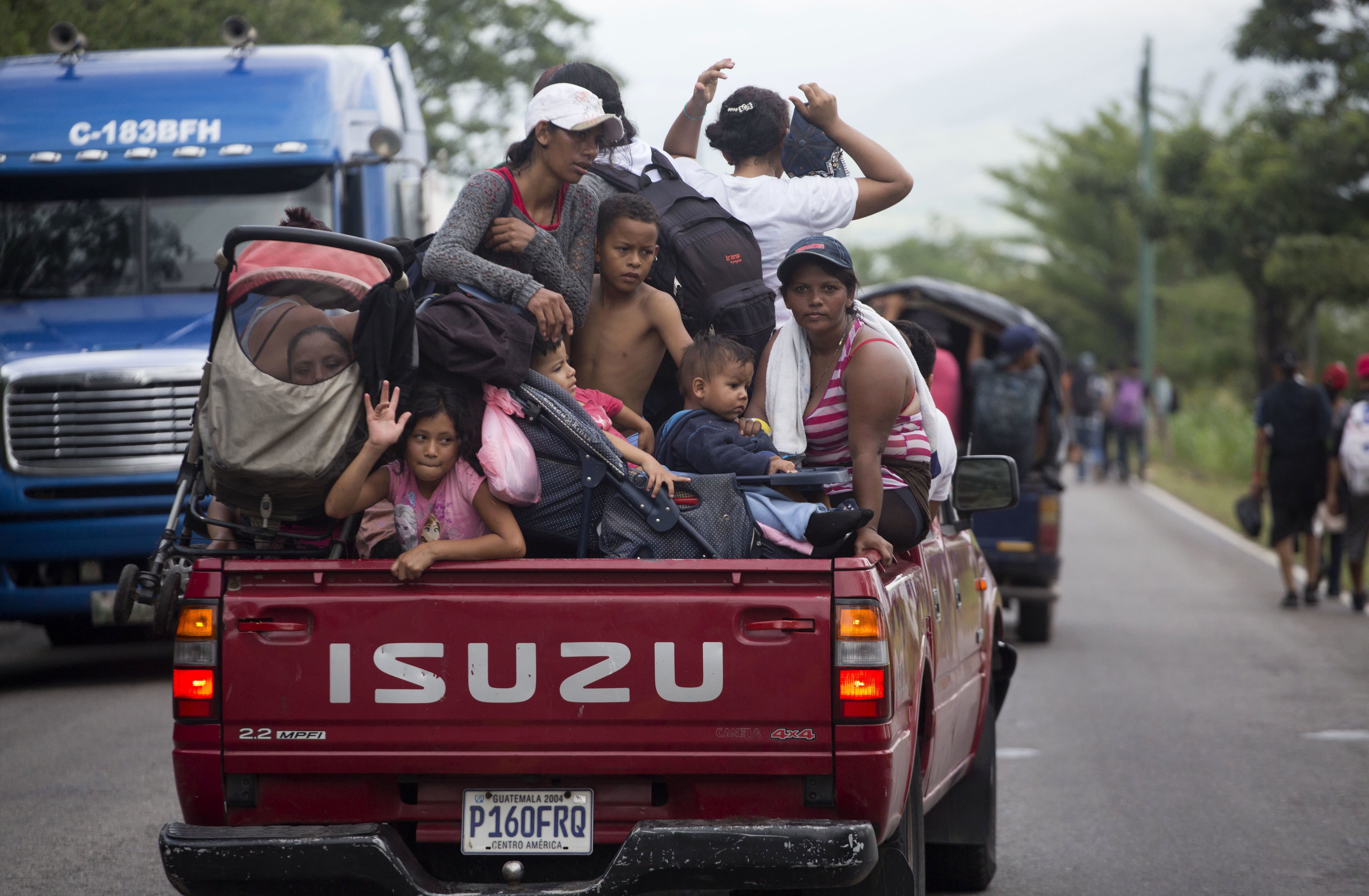 Honduran migrants who are traveling to the U.S. as a group get a free ride in the back of a driver's truck as they make their way through Zacapa, Guatemala, Wednesday, Oct. 17, 2018. The group of some 2,000 Honduran migrants hit the road in Guatemala again Wednesday, hoping to reach the United States despite President Donald Trump's threat to cut off aid to Central American countries that don't stop them. (AP Photo/Moises Castillo)