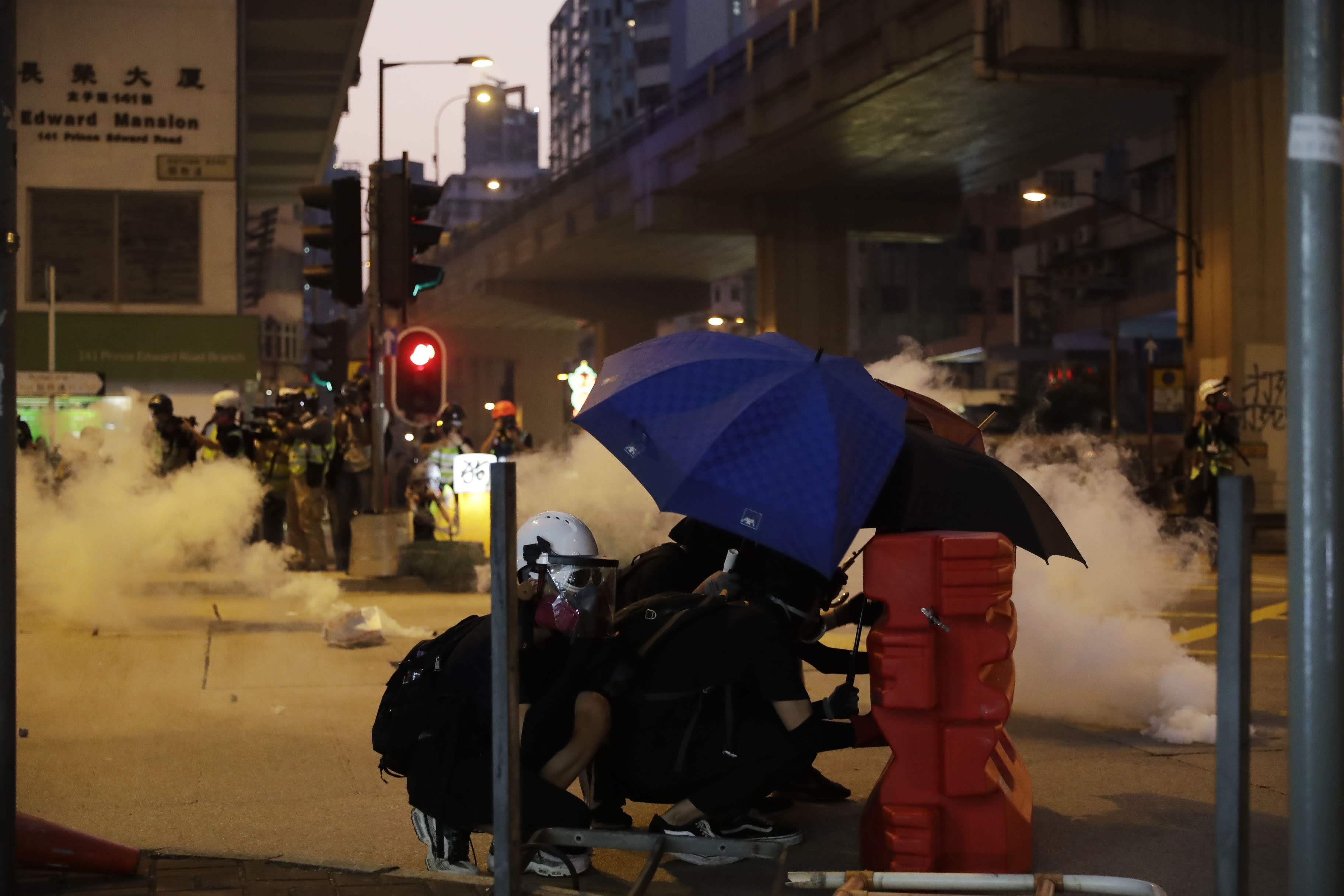 Protestors face police tear smoke in Hong Kong, Sunday, Oct. 20, 2019. Hong Kong protesters again flooded streets on Sunday, ignoring a police ban on the rally and setting up barricades amid tear gas and firebombs. (AP Photo//Mark Schiefelbein)