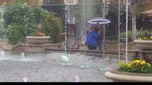 Elderly couple dances in the rain