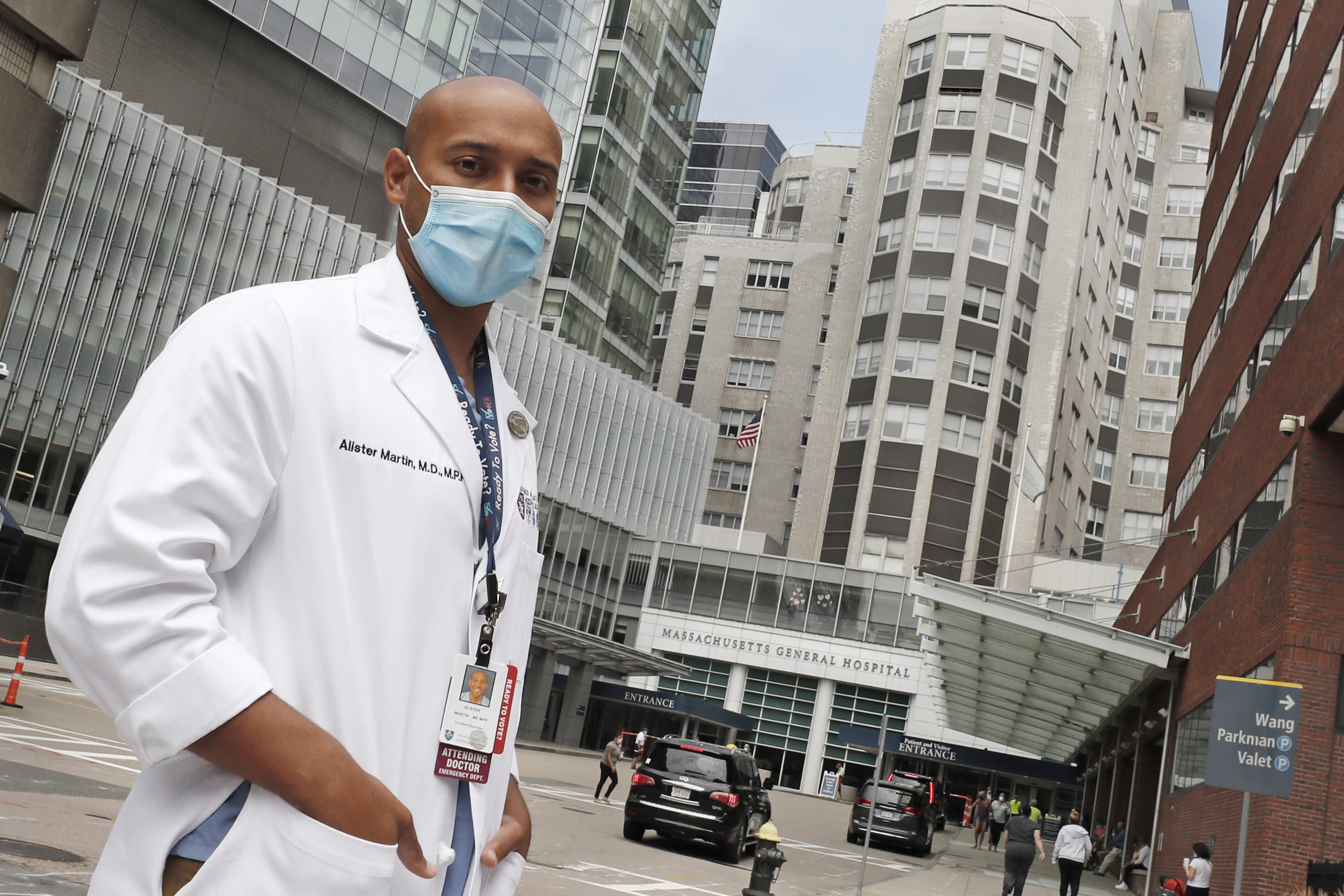 """Alister Martin, an emergency room doctor at Massachusetts General Hospital, poses outside the hospital, Friday, Aug. 7, 2020, in Boston. Martin founded the organization """"VotER"""" to provide medical professionals voter registration resources for patients who are unregistered voters. (AP Photo/Charles Krupa)"""