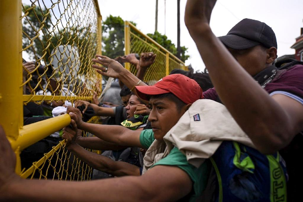Mexican authorities have reinforced the metal gate holding back Honduran migrants after a previous group broke through a weaker barrier