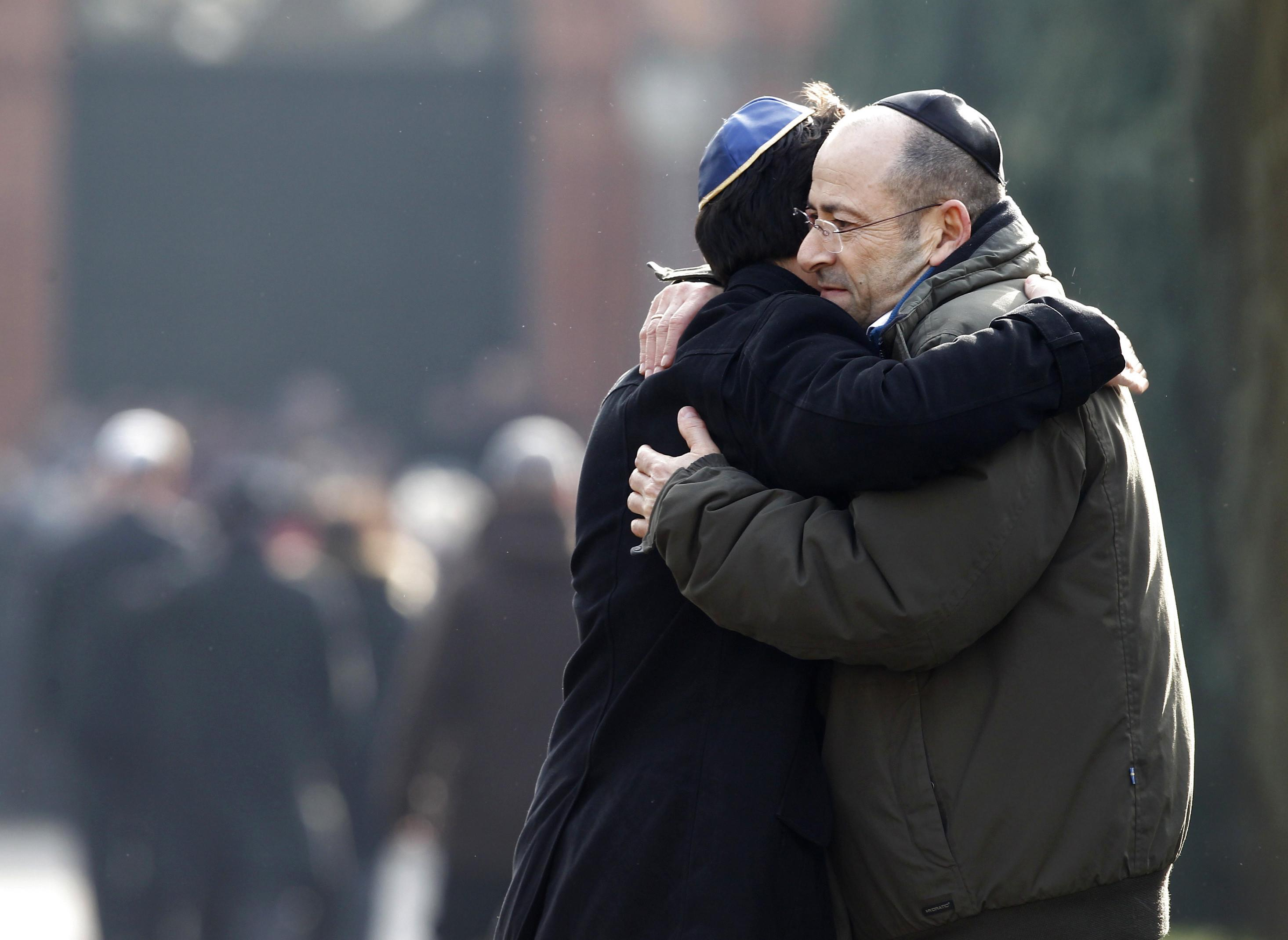 Two men wearing kippahs hug each other prior to the burial of a Jewish victim of the attacks, at the Vestre Kirkegaard cemetery in Copenhagen, Denmark, on February 18, 2015 (AFP Photo/Bax Lindhardt)