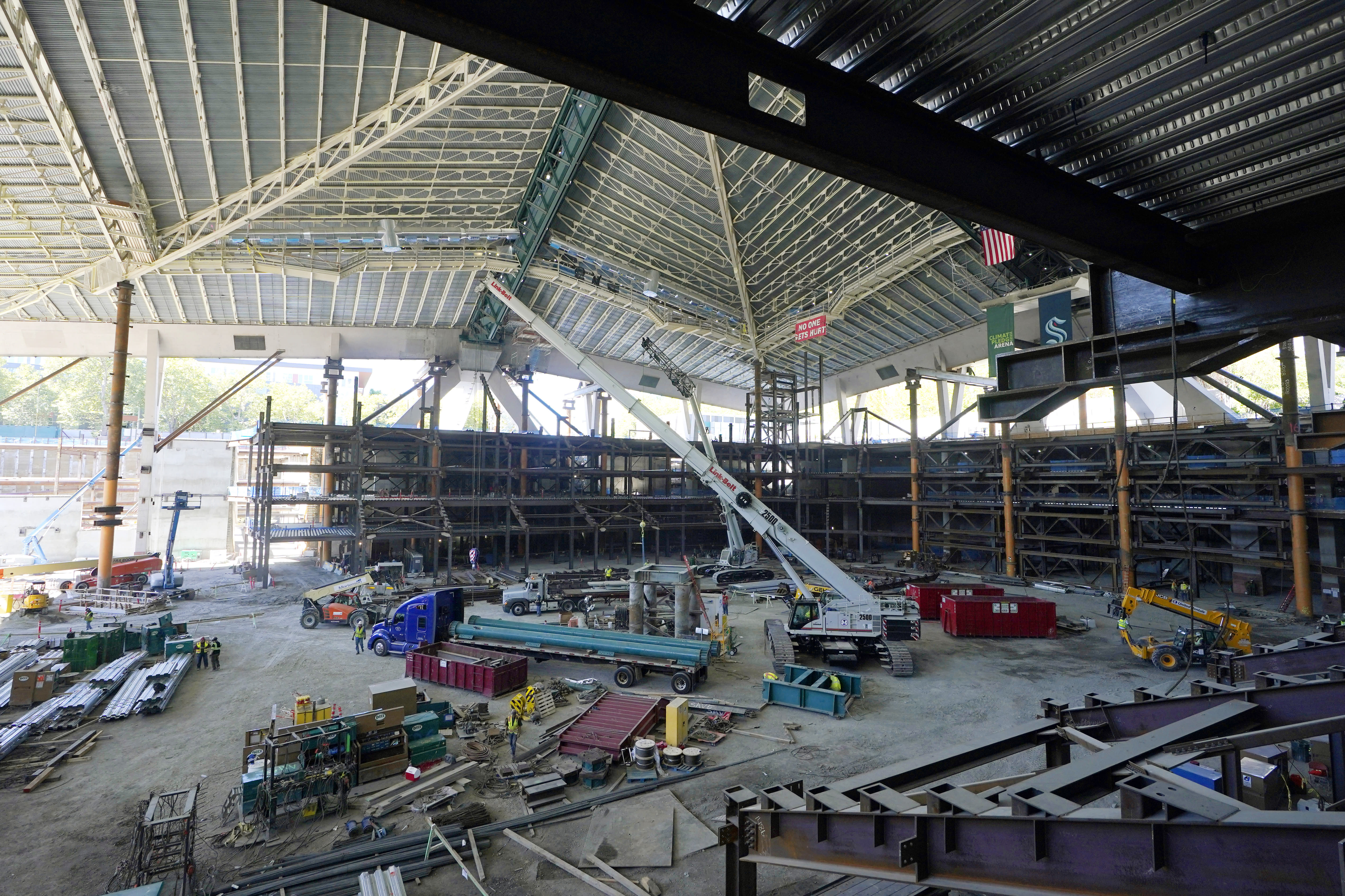 The historic roof of the former KeyArena and a tiered seating area tower over trucks and a crane working Tuesday, Sept. 1, 2020, at what will be center-ice of the Climate Pledge Arena in Seattle, as viewed from the club level of the home of the Seattle Kraken NHL hockey team. Sometime in the late summer or early fall of 2021, the Kraken will open the new facility -- at a cost that will likely total $1 billion by the time it's done -- and become the NHL's 32nd franchise. (AP Photo/Ted S. Warren)
