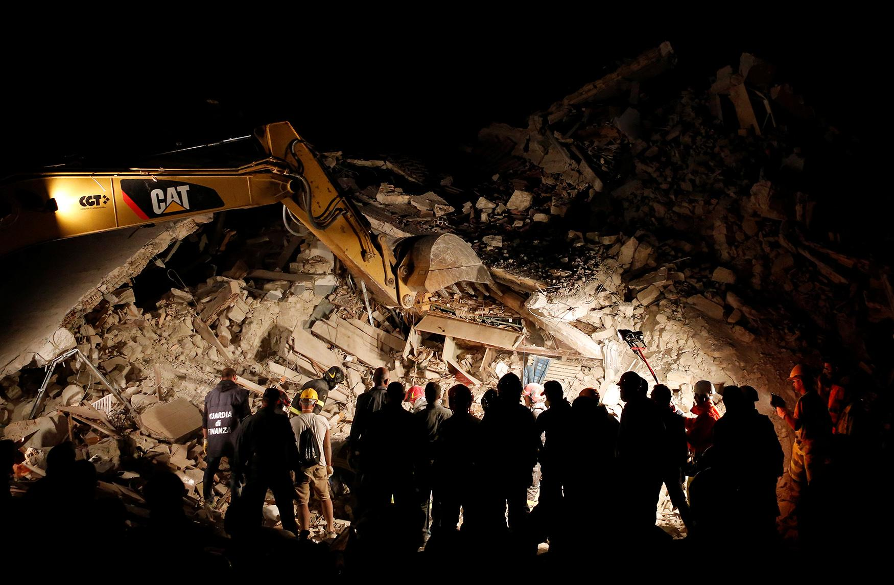 <p>Rescuers work in the night at a collapsed house following an earthquake in Pescara del Tronto, central Italy, August 24, 2016. (Photo: Remo Casilli/Reuters) </p>