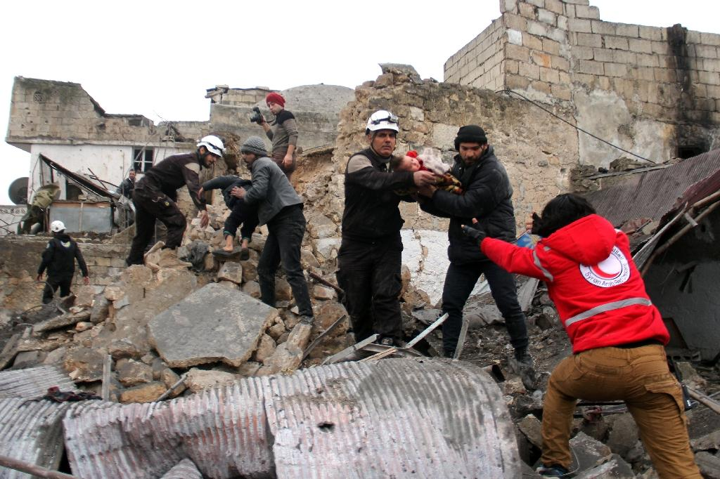 Syrian Civil Defence volunteers rescue children from a damaged building following a reported airstrike that targeted the Idlib bus station on January 18, 2017 (AFP Photo/Omar haj kadour)