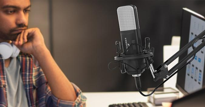Stock image of a man sitting in front of a studio mic.