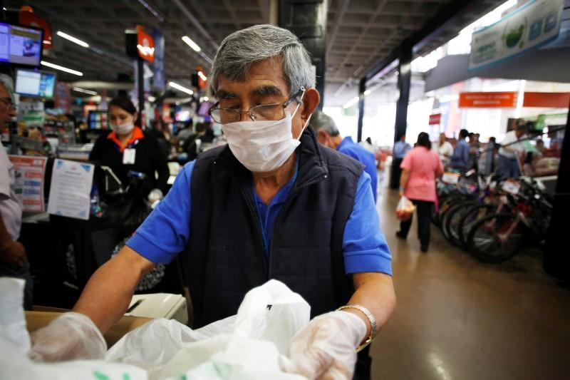 An elderly man, working as a packer at a supermarket, wears a protective face mask as a security measure for the coronavirus disease (COVID-19), in Mexico City