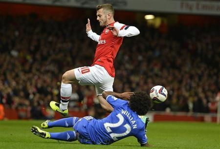 Arsenal's Wilshere is challenged by Chelsea's Willian during their English League Cup fourth round soccer match at Emirates Stadium in London