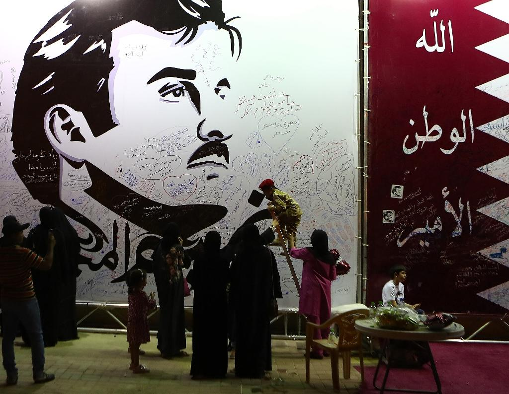 Qataris write comments on a wall bearing a portrait of Emir Sheikh Tamim bin Hamad Al Thani on July 06, 2017