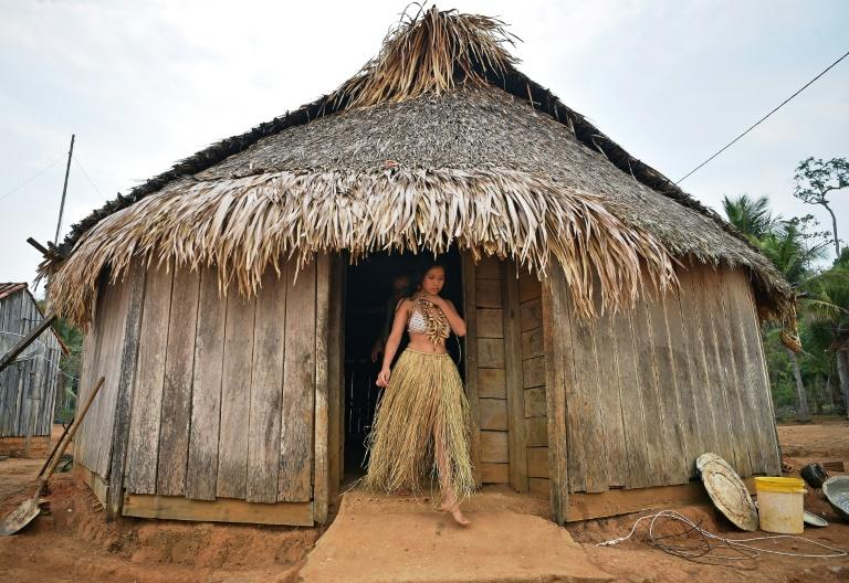 A young woman emerges from a hut in the tribe's reserve in the Amazon, south of Porto Velho, Brazil (AFP Photo/CARL DE SOUZA)