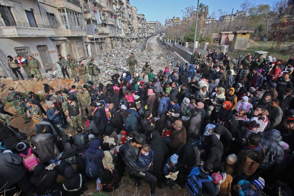 Syrian residents fleeing the violence gather at a checkpoint, manned by pro-government forces, in the Maysaloun neighbourhood of the northern embattled Syrian city of Aleppo on December 8, 2016 (AFP Photo/Youssef KARWASHAN)