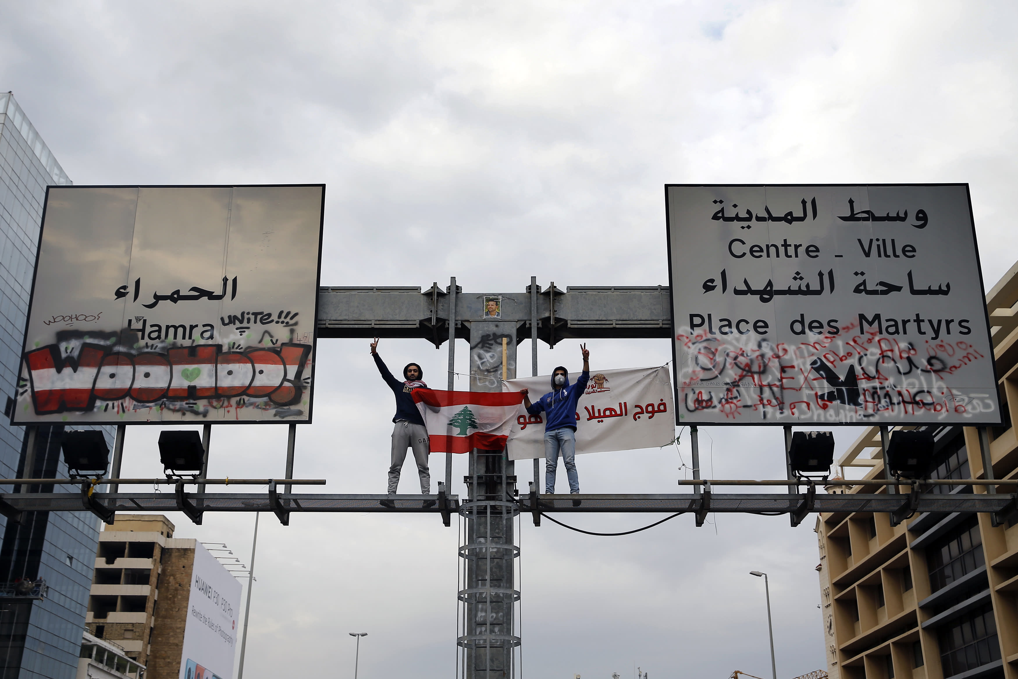 Anti-government protesters stand atop a road sign and flash the victory sign as others block a main highway in Beirut, Lebanon, Friday, Jan. 17, 2020. Protesters closed major roads in the capital Beirut and around wide parts of Lebanon paralyzing the country as the political crisis over the formation of a new government worsens. (AP Photo/Bilal Hussein)