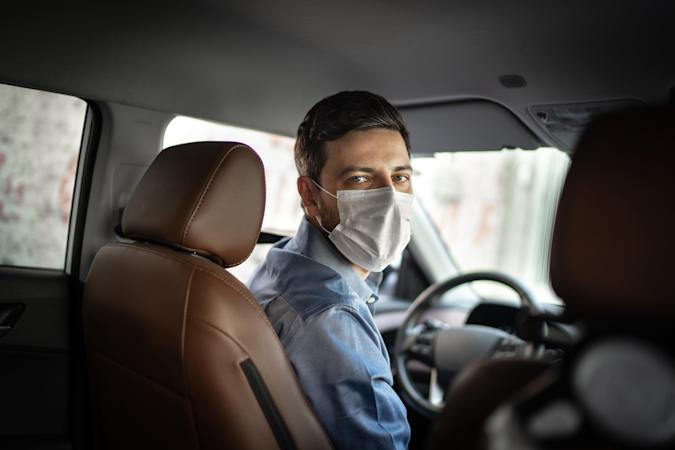 Driver taking to a passenger on seat back wearing protective medical mask