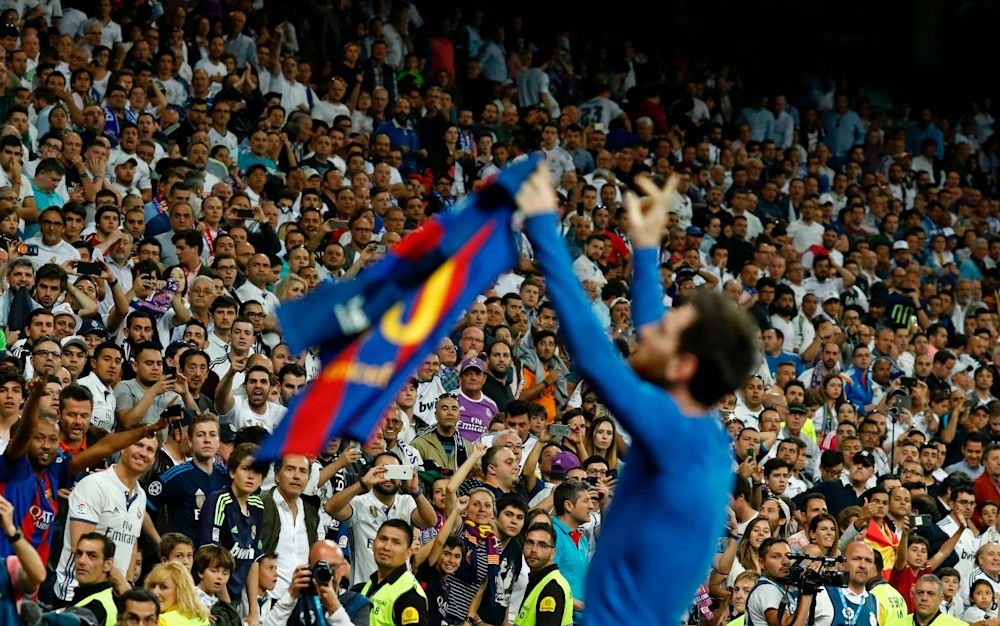 Lionel Messi holds up his shirt to the travelling Barcelona fans - AFP
