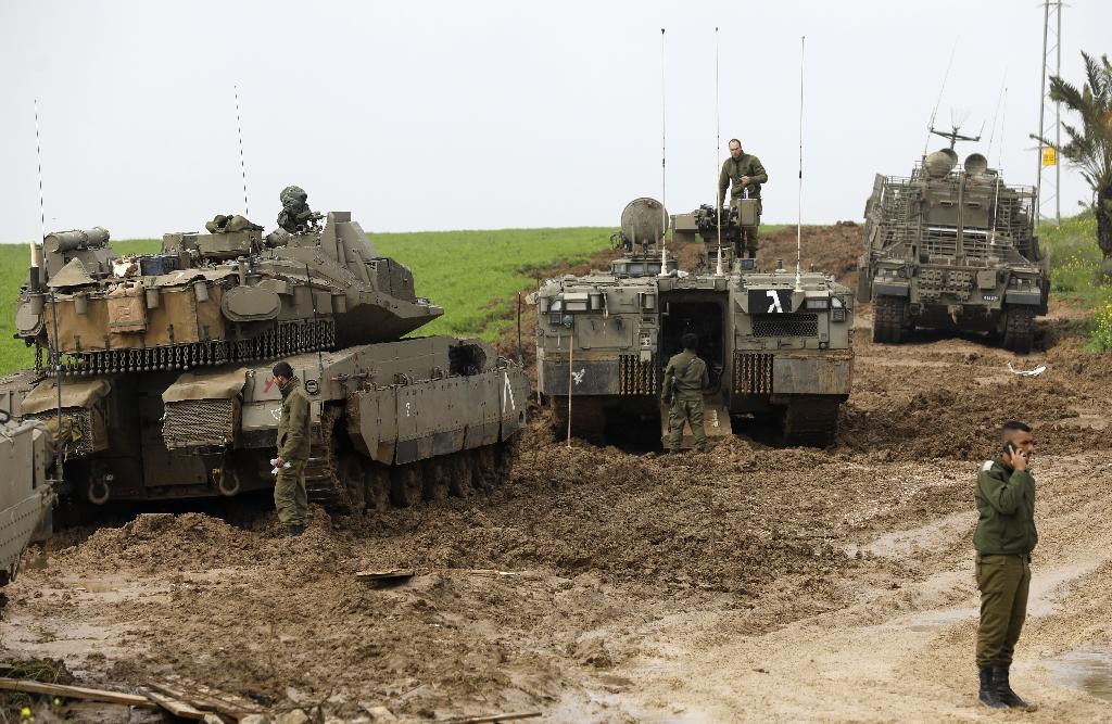Israeli tanks monitor the security fence on the volatile border with Gaza on February 18, 2018