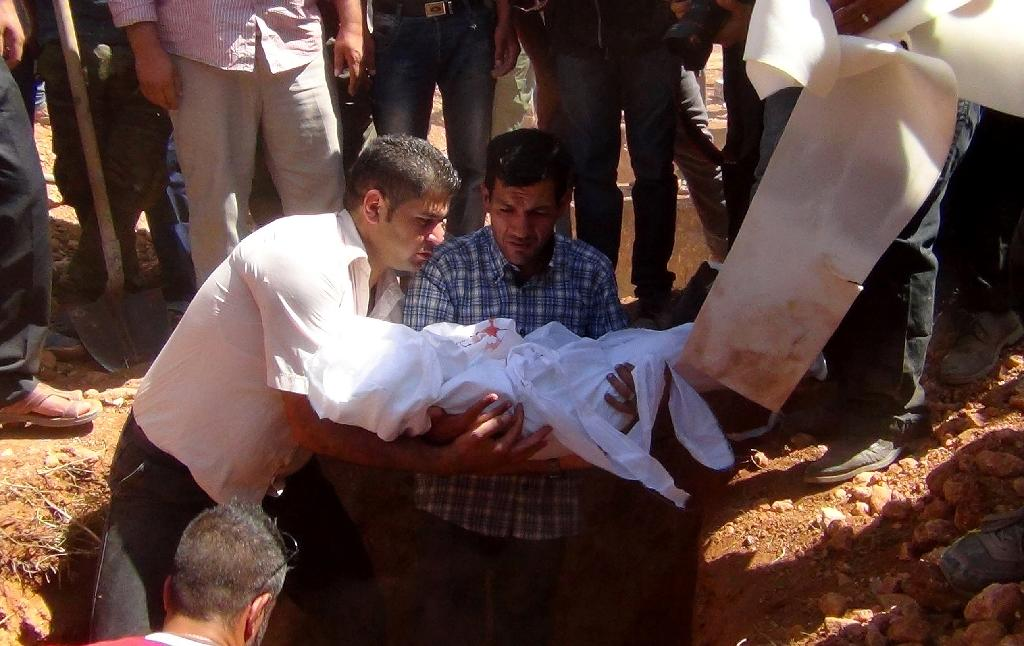 The father of toddler Aylan Kurdi, whose lifeless body on a Turkish beach became a symbol of the refugee crisis, holds the body of his child during a funeral ceremony in Kobane, Syria, on September 4, 2015 (AFP Photo/ANHA)