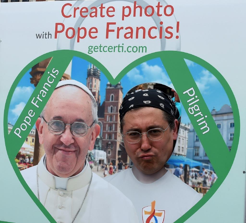 A piligrim poses with a picture installation of Pope Francis at the market square in Krakow, Poland, on July 25, 2016 (AFP Photo/Janek Skarzynski)