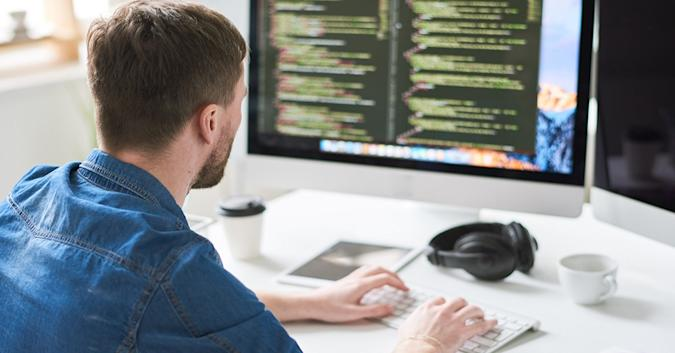 Stock image of a man writing code on a Mac.