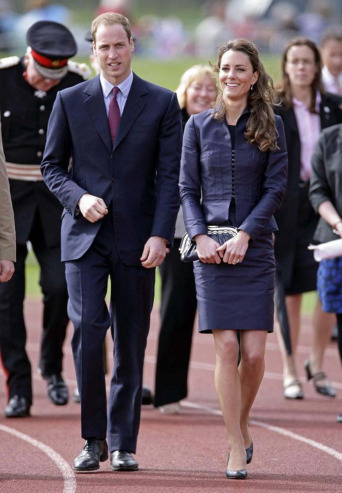 The dashing couple matched in navy blue suits while visiting an athletic track in Darwen, England.
