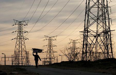 A woman carries fire wood on her head as she walks below Eskom's Elecricity pylons in Soweto,South Africa