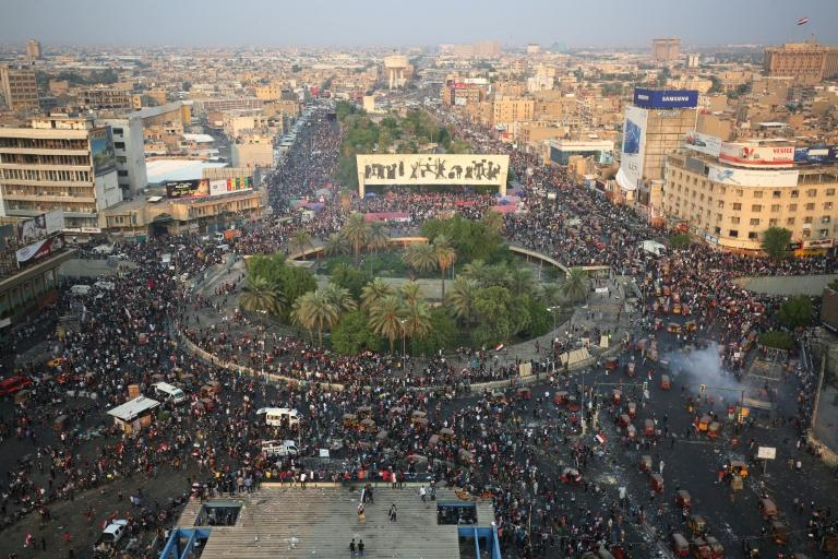 Iraqi demonstrators stand at Tahrir Square in Baghdad in October 2019 anti-government demonstrations