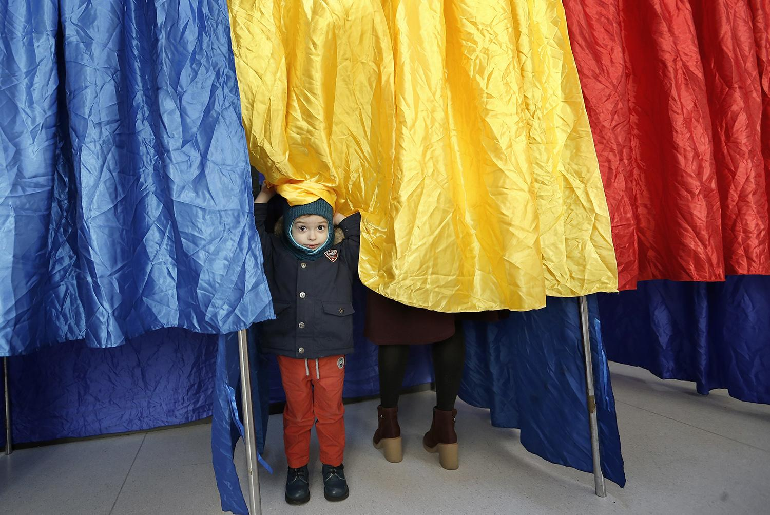 <p>A Romanian boy plays with the curtain of the polling booth, in which his mother is stamping her ballot, at Cezar Bolliac Gymnasium School polling station, in Bucharest, Romania, Dec. 11, 2016. (Photo: ROBERT GHEMENT/EPA) </p>