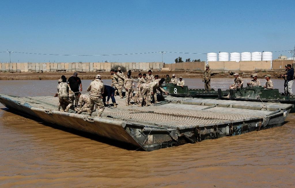 International coalition forces and Iraqi soldiers install a floating bridge at the Taji camp, north of Baghdad, during a training session ahead of installing replacement bridges in Mosul, on March 6, 2017 (AFP Photo/SABAH ARAR)