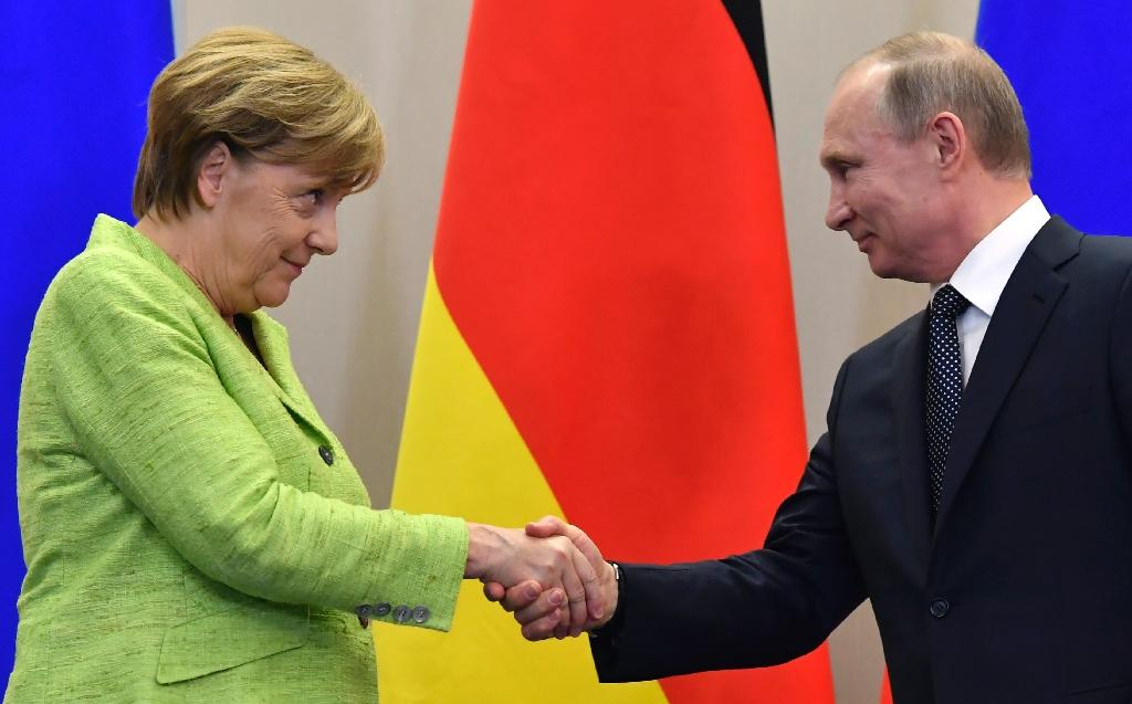 Russian President Vladimir Putin shakes hands with German Chancellor Angela Merkel following their meeting at the Bocharov Ruchei state residence in Sochi, on May 2, 2017