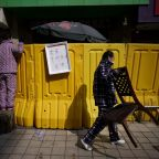 Shoppers shout over the wall in China's Wuhan
