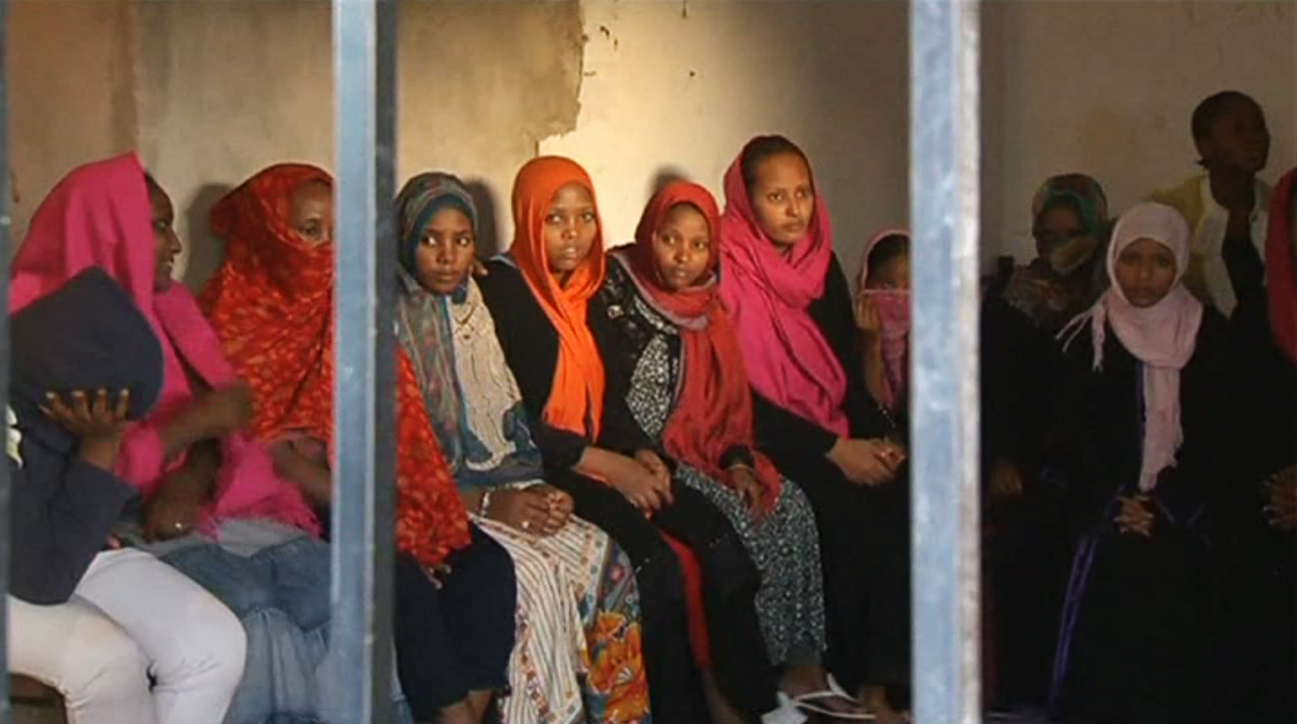 In this image made from Monday, Oct. 14, 2013 video, migrants look through bars at Sabratha migrant detention center for women in Sabratha, Libya. Libya's chaos in the two years following the overthrow of dictator Moammar Gadhafi has turned the country into a prime springboard for tens of thousands of migrants, mainly from Africa, trying to reach Europe in dangerous sea voyages. (AP Photo/AP Video)