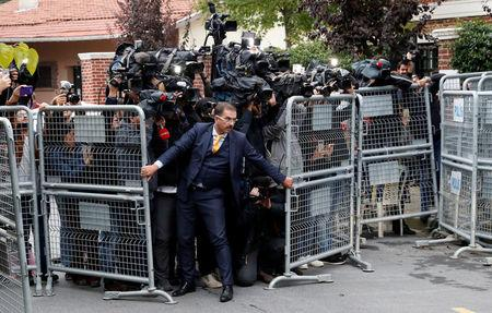 A security official holds barriers during the arrival of Saudi officials at Saudi Arabia's consulate in Istanbul