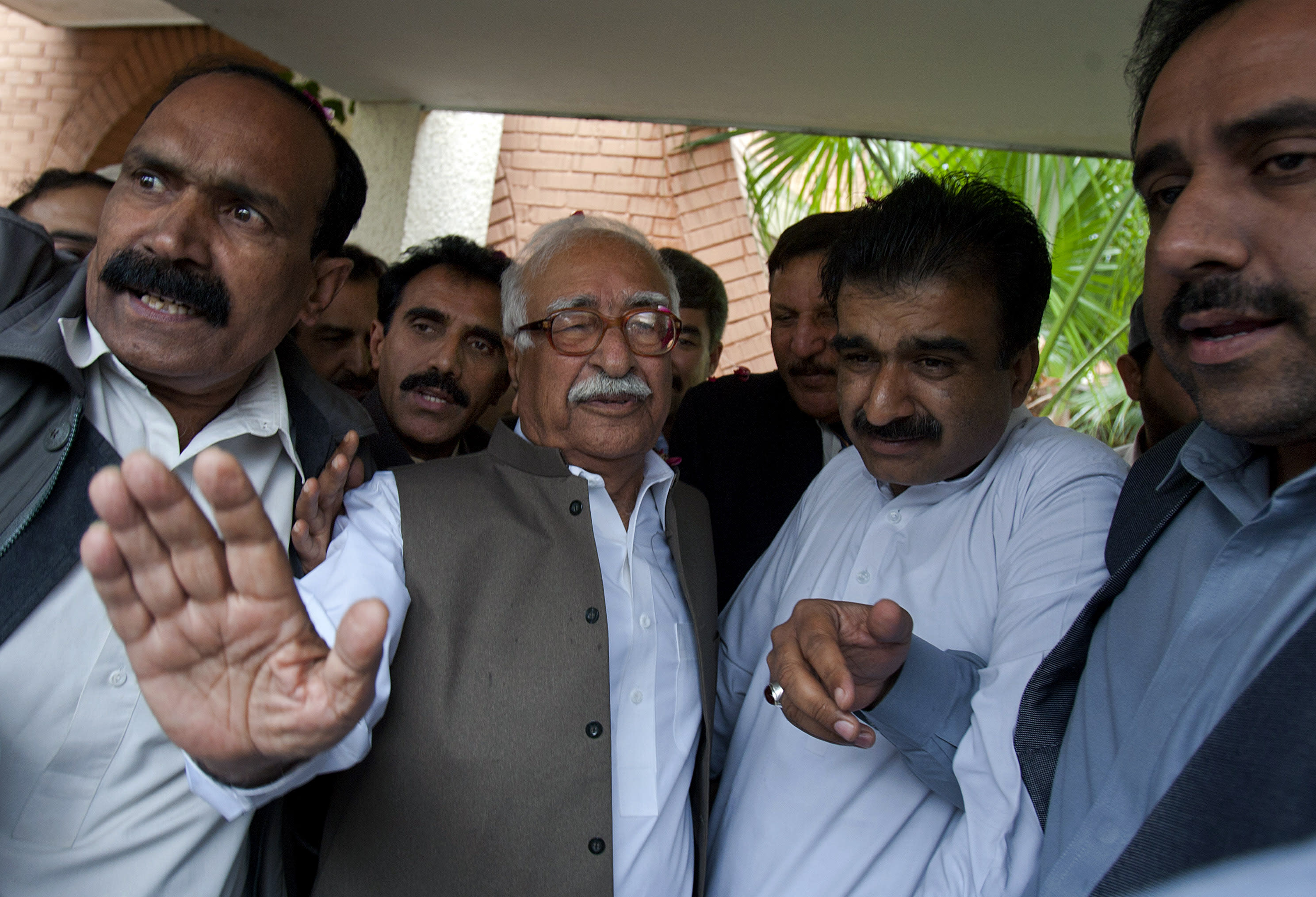 Mir Hazar Khan Khoso, center, nominated for Pakistan's caretaker prime minister, waves as he arrives to brief members of the media in Islamabad, Pakistan, Sunday, March 24, 2013. Pakistan's election commission has chosen a former high court chief justice Khoso nominated by the country's outgoing ruling party to serves as caretaker prime minister in the run up to a historic national election this spring. (AP Photo/Anjum Naveed)