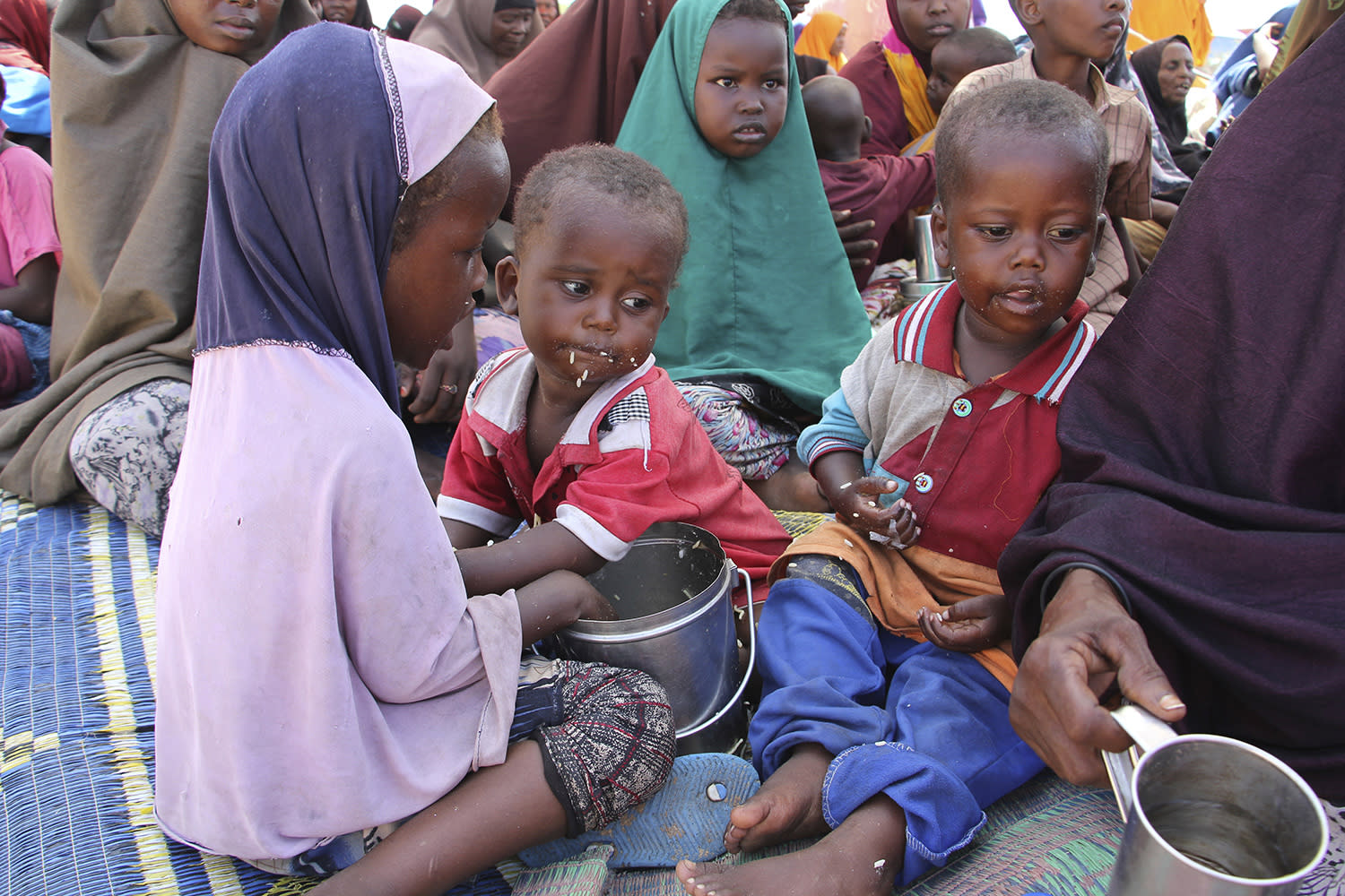 <p>Newly displaced children eat food as they sit on the ground, just outside of Mogadishu, in Somalia, Monday, March, 27, 2017. Somalia's drought is threatening 3 million lives, according to the U.N. In recent months, aid agencies have been scaling up their efforts but they say said more support is urgently needed to prevent the crisis from worsening. (Farah Abdi Warsameh/AP) </p>