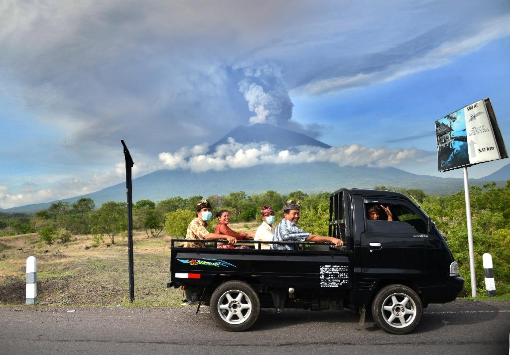 Balinese people ride on an open car past Mount Agung erupting seen from Kubu sub-district in Karangasem Regency, on Indonesia's resort island of Bali on November 27, 2017 (AFP Photo/SONNY TUMBELAKA)