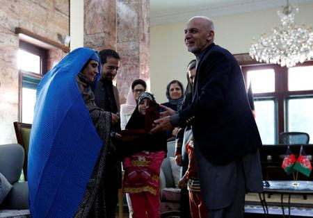 "Sharbat Gula (L), the green-eyed ""Afghan Girl"" whose 1985 photo in National Geographic became a symbol of her country's wars, receives a key to an apartment from Afghanistan's President Ashraf Ghani, after she arrived in Kabul, Afghanistan November 9, 2016. REUTERS/Mohammad Ismail"